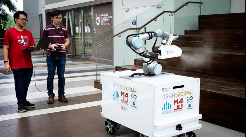 The eXtreme Disinfection roBOT (XDBOT), a semi-autonomous robot, disinfects a table in a cafeteria of the Nanyang Technological University Smart Campus in Singapore. (Photo | AFP)