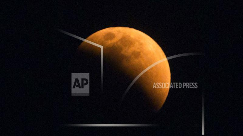 The moon turns a reddish hue as it passes through the earth's shadow during a lunar eclipse as seen in Gauhati, India.