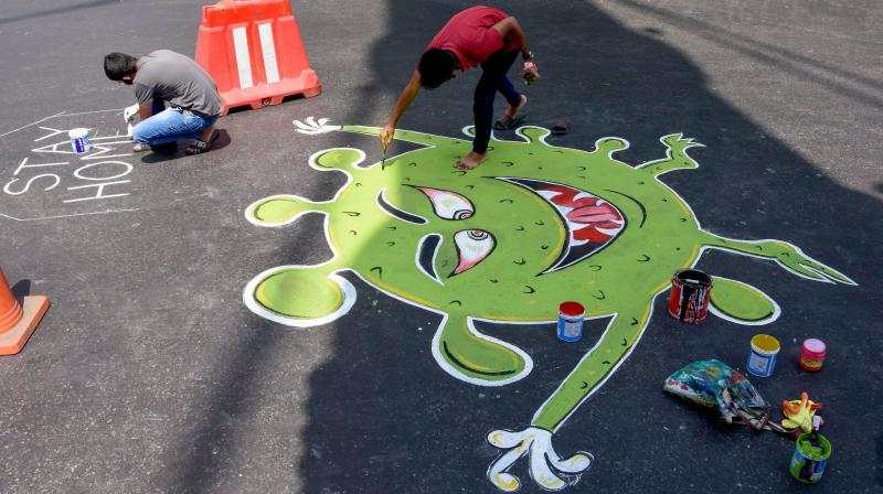 Artists paint on a street at Nana Chowk during a nationwide lockdown in the wake of coronavirus outbreak, in Mumbai. PTI photo