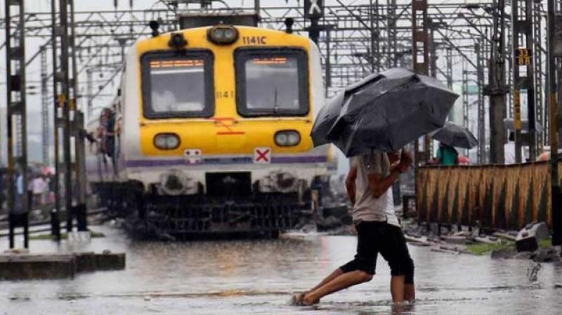 Heavy rains lashed Mumbai on Tuesday bringing rail and road transport to a screeching halt. (Photo: PTI)