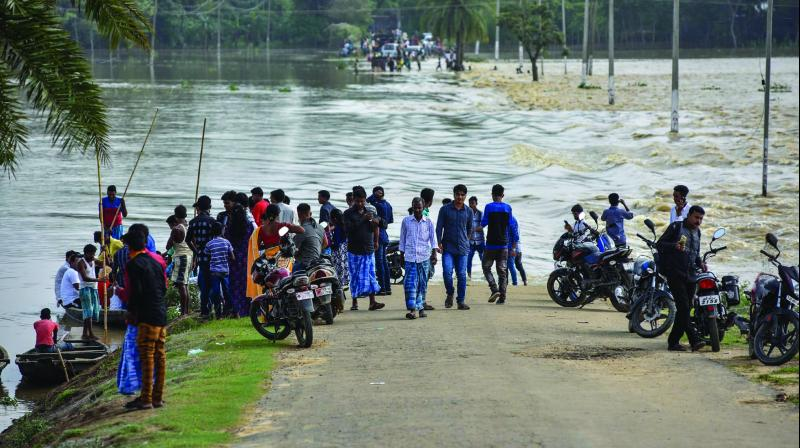 Villagers stand near a partially-submerged road in flood-affected Hojai district of Assam on Saturday. (Photo: PTI)