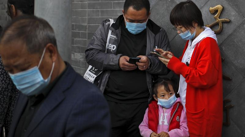 A child wearing a face mask to help curb the spread of the coronavirus looks as masked people browsing their smartphones near Forbidden City in Beijing. (AP)