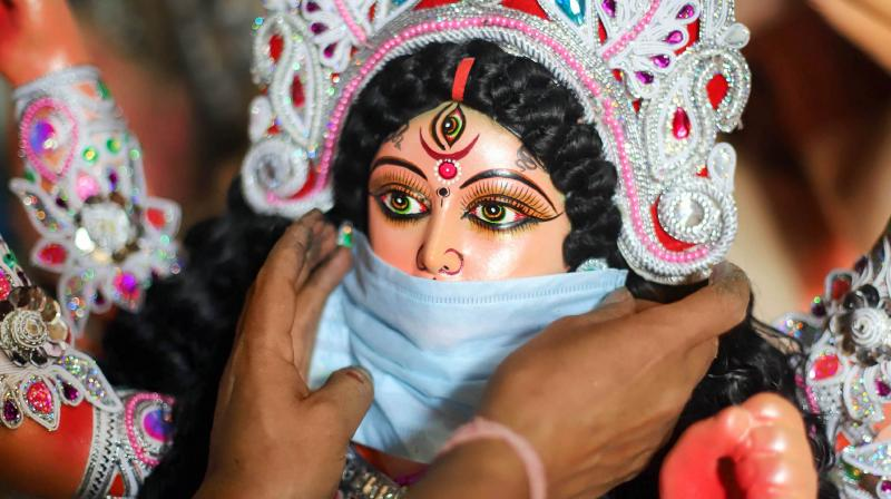 A devotee puts a mask on the face of a Goddess Durga idol to aware people against COVID-19, at a community puja pandal, in Prayagraj. (PTI)