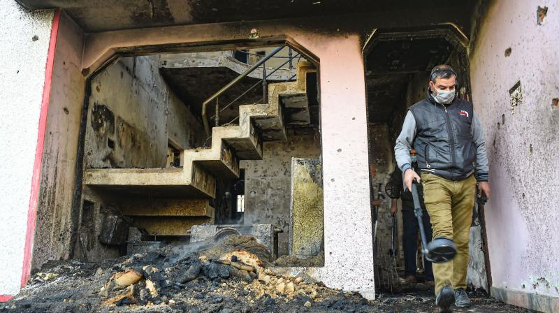 A member of the bomb disposal squad of Jammu & Kashmir police searches for an explosive material inside a damaged house after an encounter between security forces and militants, at Mouchwa on the outskirts of Srinagar, Wednesday, Oct. 28, 2020. Two militants were killed in the gunfight. (PTI)