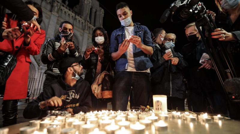 People lights candle outside the Notre-Dame de l'Assomption Basilica in Nice on October 29, 2020 in tribute to the three victims of a knife attacker, cutting the throat of at least one woman, inside the church of the French Riviera city. (AFP)