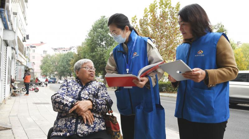 Census workers collect information from a woman in Lianyungang, in China's eastern Jiangsu province on November 1, 2020, as millions of census-takers began knocking on doors for a once-a-decade head count of the world's largest population that for the first time will use mobile apps to help crunch the massive numbers. (AFP)