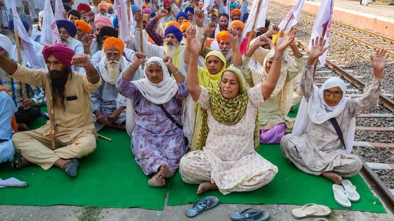 Farmers shout slogans during their ongoing 'Rail Roko' protest over new farm laws, at Jandiala Guru in Amritsar. (PTI)