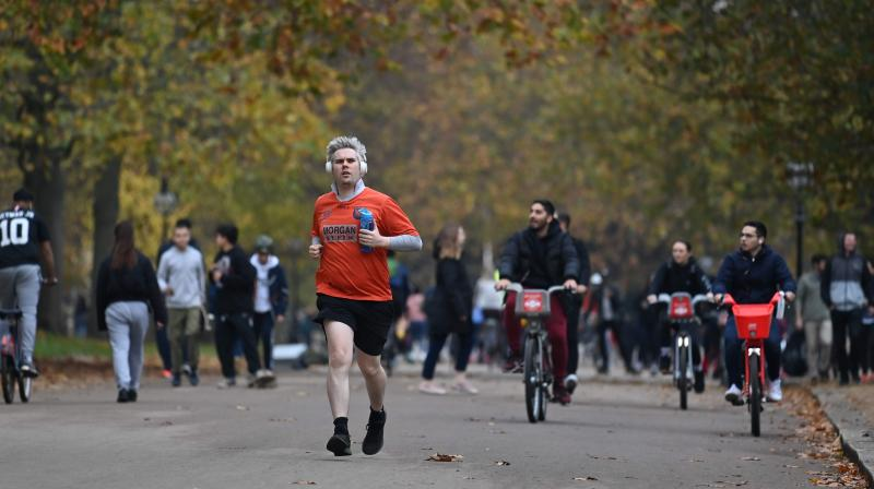 People exercise in Green Park in central London on November 8, 2020 during a second national lockdown designed to contain soaring infections of the novel coronavirus. (AFP)