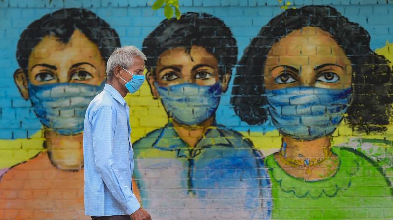 A man wearing mask walks past a mural, in New Delhi, Sunday, Nov 8, 2020. (PTI)