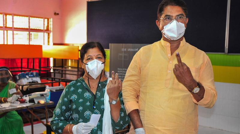 Karnataka Revenue Minister R Ashoka and his wife Pramilarani show their fingers marked with indelible ink after casting their votes for the state by-polls, at Rajarajeshwari Nagar in Bengaluru. (PTI)
