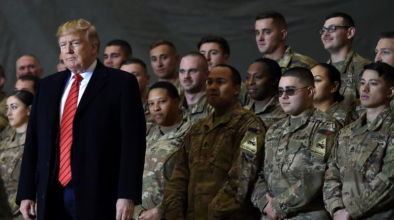US President Donald Trump speaks to the troops during a surprise Thanksgiving day visit at Bagram Air Field, on November 28, 2019 in Afghanistan. - The US will cut its troops in Afghanistan to 2,500 in January, the lowest level in nearly two decades of war, as outgoing President Donald Trump follows through on a pledge to end conflicts abroad, the Pentagon announced on November 17, 2020. (AFP)