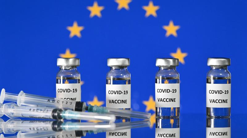 An illustration picture shows vials with Covid-19 Vaccine stickers attached, and syringes, with a flag of the European Union, on November 17, 2020. (AFP)