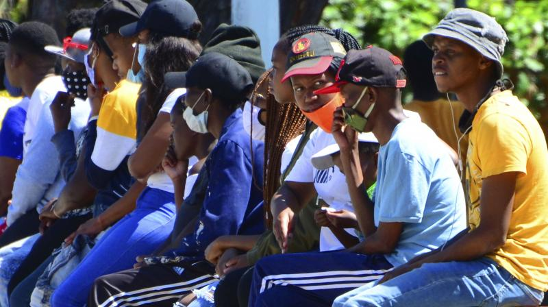 Without practicing social distancing, people queue for social grant payments at a post office in Port Elizabeth, South Africa, Friday, Nov. 13, 2020. The African continent has surpassed 2 million confirmed cases of COVID-19 as health officials warn of infections starting to creep up again into a second surge. (AP)