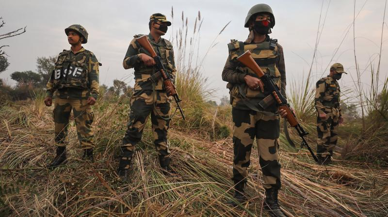 Security personel stand gurad beside an underground tunnel near the international border in Samba sector, suspected to have been used by terrorists killed in a recent encounter in Nagrota, in Jammu district. (PTI)