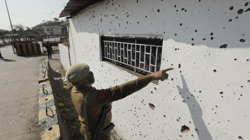 Jammu & Kashmir police personnel show a damaged wall of a police post after an encounter in Nagrota yesterday, in Jammu district. (PTI)