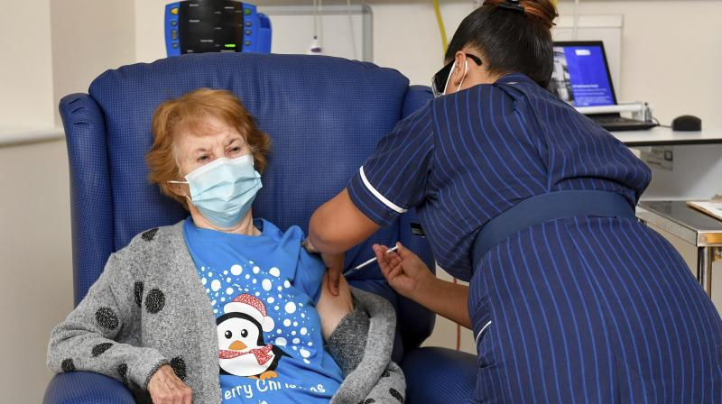 90 year old Margaret Keenan, the first patient in the UK to receive the Pfizer-BioNTech COVID-19 vaccine, administered by nurse May Parsons at University Hospital, Coventry, England, Tuesday Dec. 8, 2020. The United Kingdom, one of the countries hardest hit by the coronavirus, is beginning its vaccination campaign, a key step toward eventually ending the pandemic. (AP)