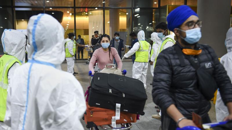 Municipal workers in personal protective equipment look on as passengers from United Kingdom arrive at the Chhatrapati Shivaji Maharaj International Airport, in Mumbai (PTI)