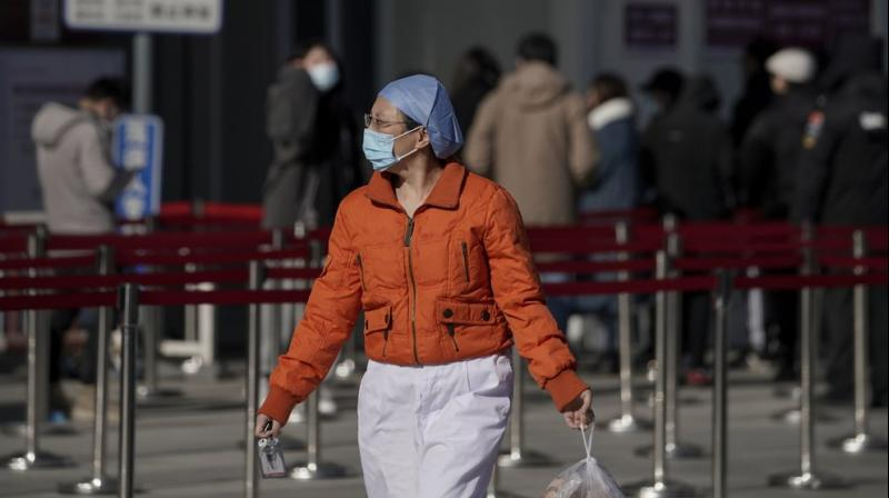 A nurse wearing a face mask to help curb the spread of the coronavirus walks by people lining up for a coronavirus test at a hospital in Beijing, Sunday, Jan. 17, 2021. The coronavirus was found on ice cream produced in eastern China, prompting a recall of cartons from the same batch, according to the government. (AP)