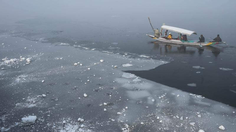 Tourist ride a shikara along a frozen part of the Dal Lake, in Srinagar, Thursday, Jan. 14, 2021. The Kashmir Valley is reeling under severe cold, as Srinagar recorded a low of minus 8.4 degrees Celsius, the lowest in the city after 29 years. (PTI)