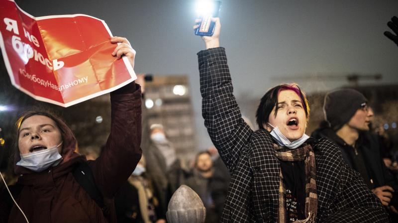 A demonstrator shines his cellphone flashlight as an other waves a poster reads