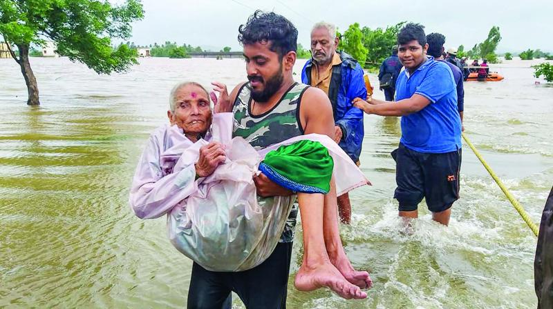 National Disaster Response Force personnel carry an elderly resident at the flood-hit area of Nilewadi in Kolhapur, Friday. (Photo: PTI)