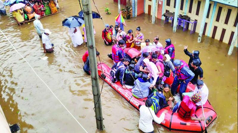 Disaster relief personnel rescue people on Friday in flood-affected Kolhapur. (Photo: PTI)