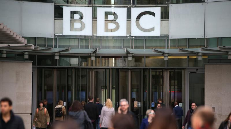 In this file photo taken on October 30, 2017 people pass the entrance of the headquarters of the British Broadcasting Corporation (BBC) in London. - BBC on Thursday February 11, says it is 'disappointed' at China banning its news channel. (Daniel LEAL-OLIVAS / AFP)