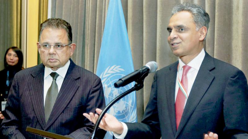 India's permanent representative to the UN Syed Akbaruddin speaks during a reception in the honour of Dalveer Bhandari (left) in New York. (Photo: AP)