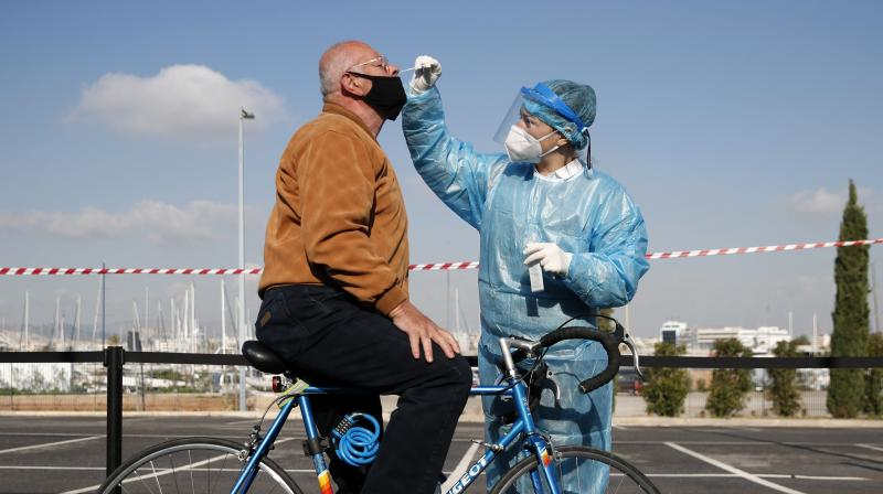 A medical staff member conducts a COVID-19 rapid test on a bicycle rider at a drive-through testing site. (Representational Image: AP)
