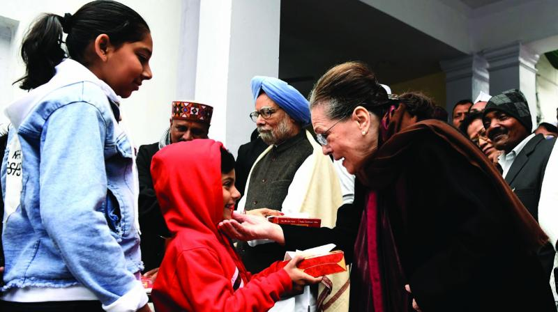 Congress president Sonia Gandhi distributes sweets to  children on the party's 135th foundation day at AICC HQ in New Delhi on Saturday. (Photo: Asian Age)