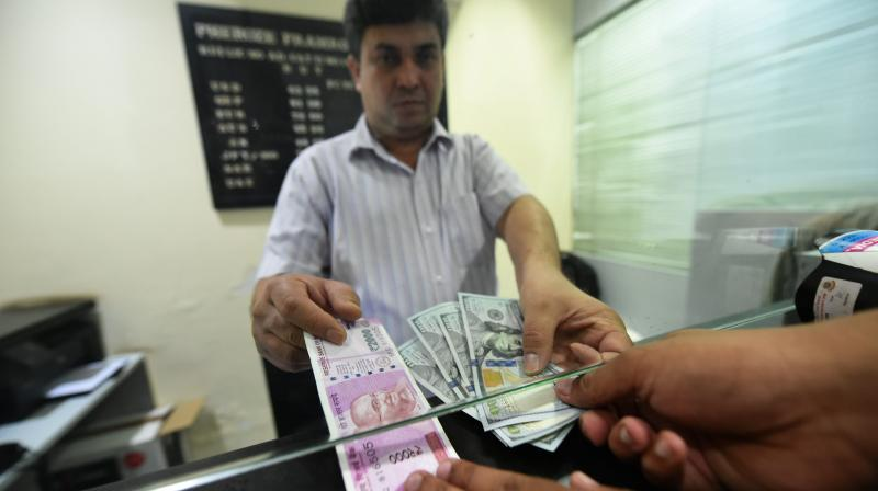 A customer exchanges currency at a forex bureau. (PTI Photo)