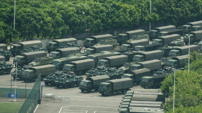 Trucks and armoured personnel carriers are seen outside the Shenzhen Bay stadium in Shenzhen, bordering Hong Kong in China's southern Guangdong province, on Thursday. (Photo: AFP)