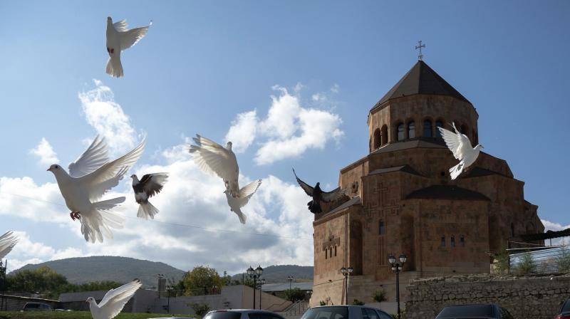 Pigeons fly near Holy Mother of God Cathedral in Stepanakert during a military conflict in the separatist region of Nagorno-Karabakh, Friday, Oct. 9, 2020. Armenia and Azerbaijan say they have agreed to a cease-fire in Nagorno-Karbakh starting at noon Saturday. (AP)