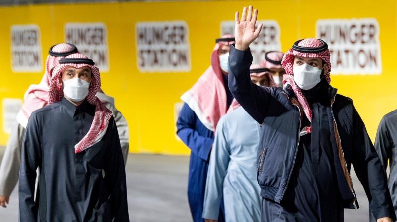 In this handout picture provided by the Saudi Royal Palace, Saudi Arabian Crown Prince Mohammed bin Salman (R) greets the public as he attends the Round 2: Diriyah E-Prix, in the Saudi capital Riyadh, on February 27, 2021. (Bandar AL-JALOUD / Saudi Royal Palace / AFP)