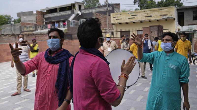 Volunteers perform a street play during an awareness campaign for COVID-19 vaccine in village Nizampur, on the outskirts of New Delhi. (Photo: AP)