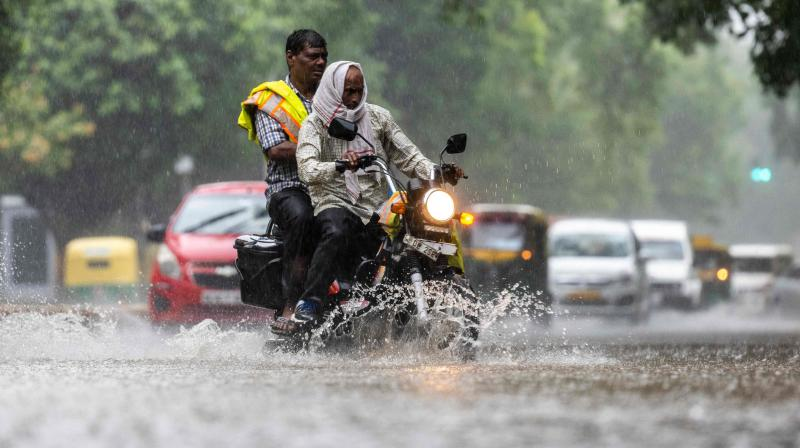 A motorcyclist drives along a waterlogged street during heavy rain in New Delhi. (Photo: AFP)