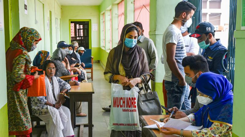 Teachers and students wait for a dose of COVID-19 vaccine during a special vaccination drive for them, at a school in Srinagar. (Photo: PTI)