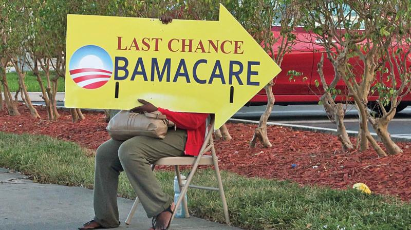 A file photo of a woman holding an Obamacare sign in front of a medical centre in Miami. (Photo: AFP)