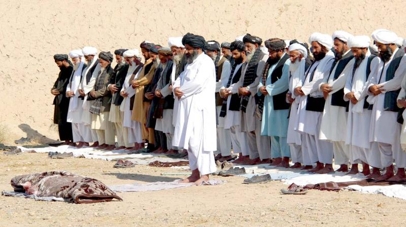 Afghan mourners pray in front of the slain Afghan local police officer in Helmand. (Photo: AFP)