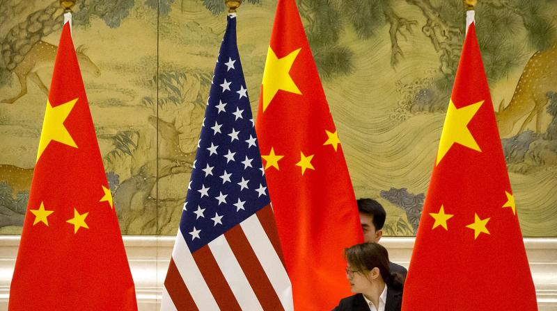 Chinese staffers adjust the U.S. and Chinese flags before the opening session of trade negotiations between U.S. and Chinese trade representatives. (Representational Image/AP)