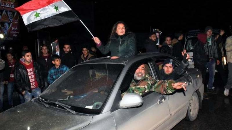 Syrians celebrate in the northern Syrian city of Aleppo, after the army said it has retaken full control of the country's second city. (Photo: AFP)