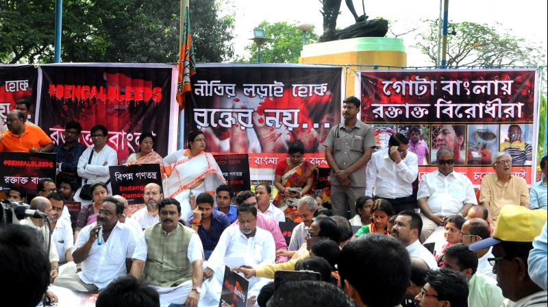 State BJP leaders and supporters at a sit-in demonstration, against the violence during the filing of nominations for the panchayat polls, in front of Gandhi statue on Mayo Road in Kolkata on Friday. (Photo: Asian Age)