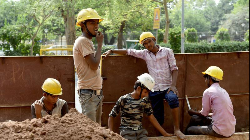 Indian labourers work at a construction site on a roadside in New Delhi. (AFP Photo)