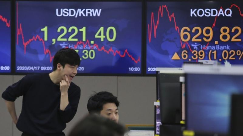 A currency trader watches monitors at the foreign exchange dealing room of the KEB Hana Bank headquarters in Seoul, South Korea, Friday, April 17, 2020. Shares have advanced in Asia after China's economic growth data, while bleak, was better than expected. (AP Photo)