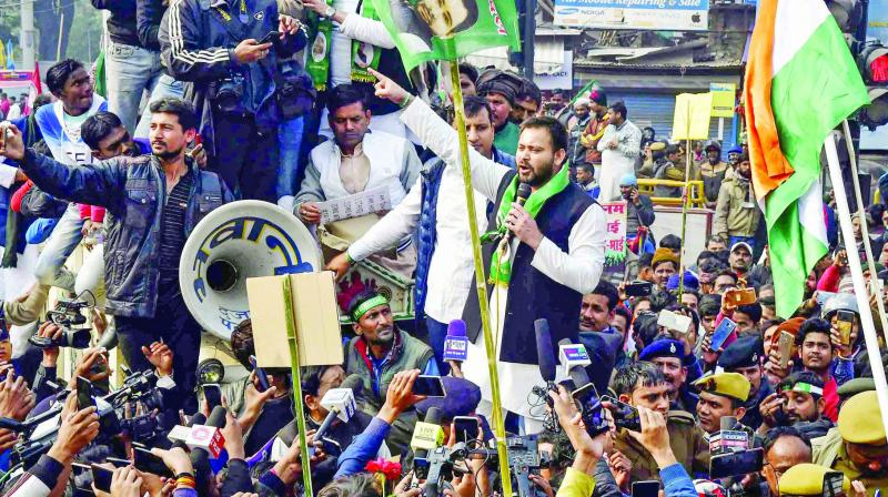RJD leader Tejashwi Yadav with supporters raises  slogans during a demonstration against NRC and Citizenship (Amendment) Act, in Patna.  (Photo: PTI)