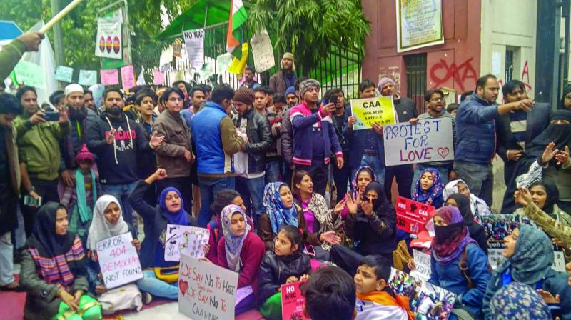 Protesters hold placards as they raise slogans during a demonstration outside Jamia Milia Islamia. (Photo: PTI)