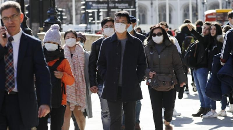 People wear protective face masks as they walk down Whitehall in the Spring sunshine in central London. (AFP)