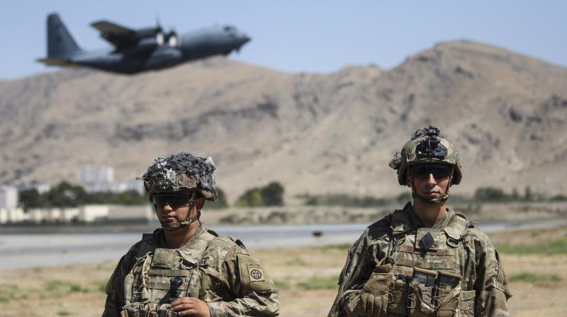 In this image provided by the Department of Defense, two paratroopers assigned to the 1st Brigade Combat Team, 82nd Airborne Division conduct security while a C-130 Hercules takes off during a evacuation operation in Kabul, Aug. 25, 2021. (Department of Defense via AP)