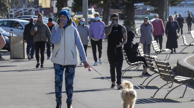 People, some wearing masks, walk along a path in Wellington, New Zealand Thursday, Aug. 19, 2021.  (Mark Mitchell/New Zealand Herald via AP)