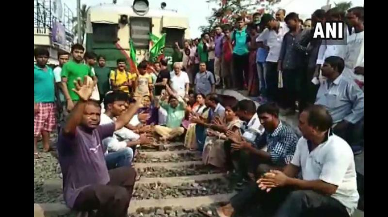 Protest against the alleged killing of party workers in Basirhat region of the district, BJP workers stopped a train by sitting on the railway tracks. (Photo: ANI)